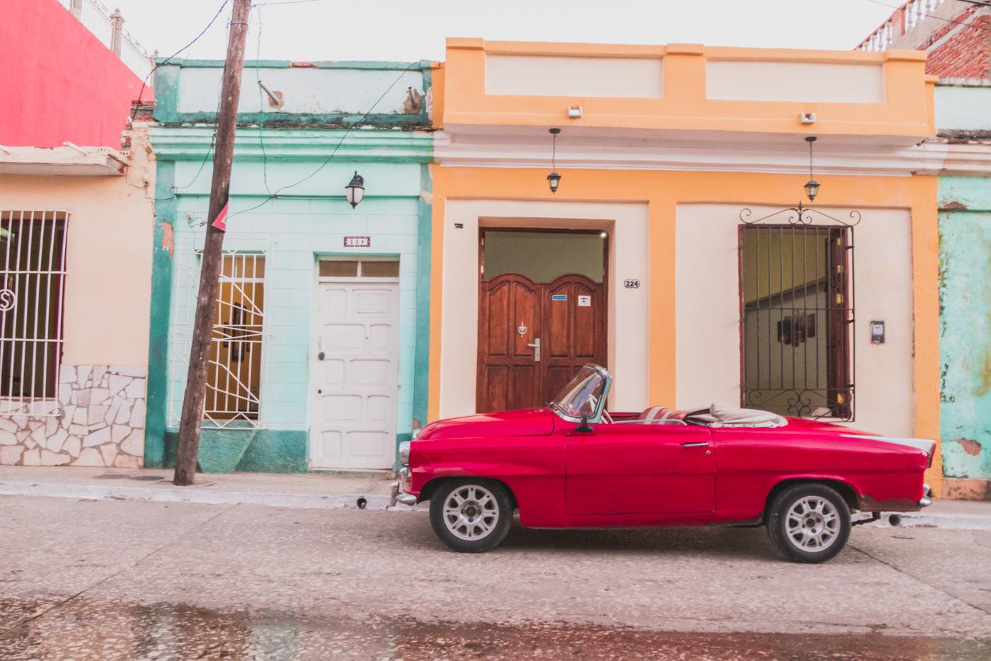 Ein roter Oldtimer vor bunten Häusern