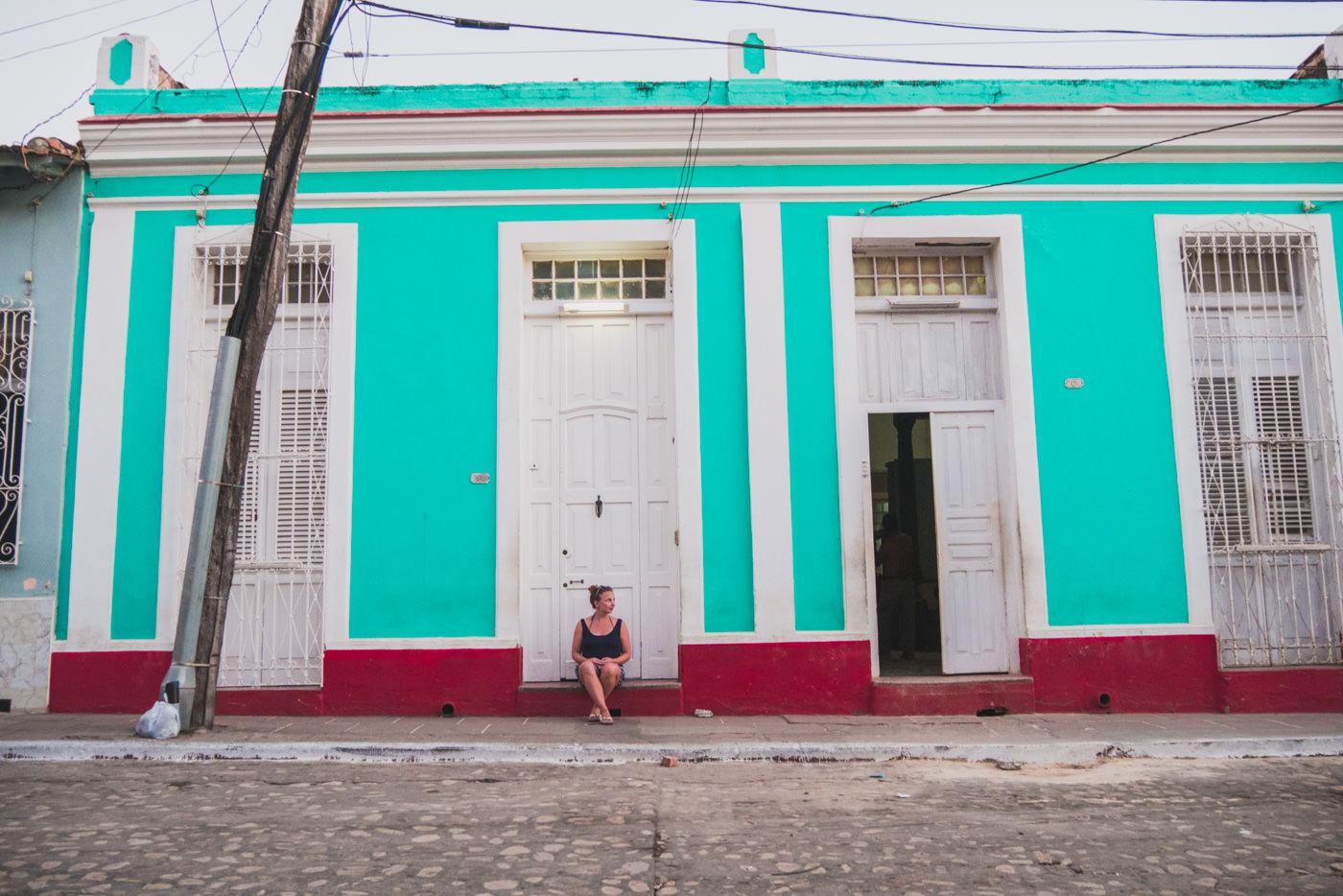 Julia vor einer bunten Hausfassade in Trinidad