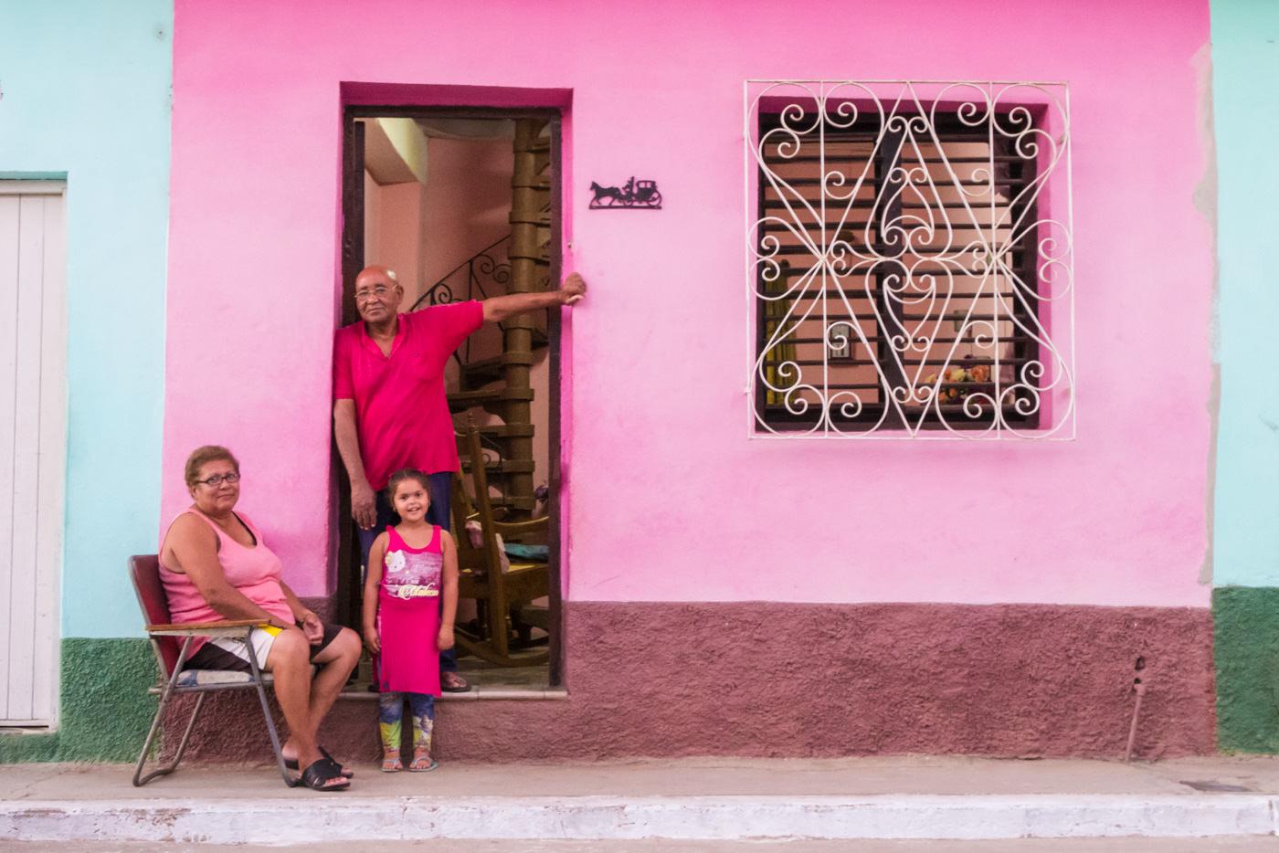 Kubanische Familie ist passend zur Farbe des Hauses gekleidet