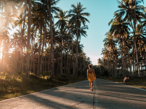 Julia auf der Straße zwischen Palmen auf Siargao, Philippinen