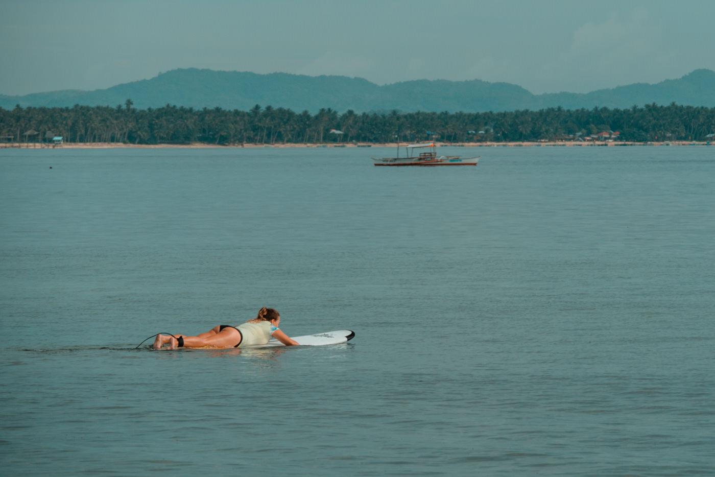 Julia paddelt raus zum surfen auf Siargao Island