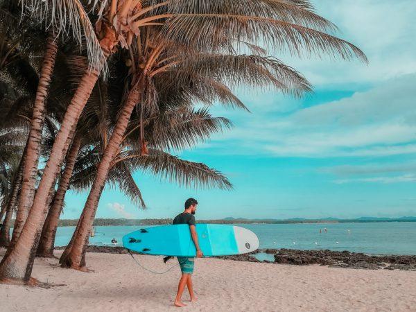 Matthias mit dem Surfbrett am Strand